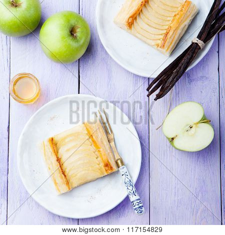 Apple tart, puff pastry strips with vanilla custard on a wooden background