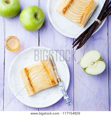 Apple tart, puff pastry strips with vanilla custard on a wooden background