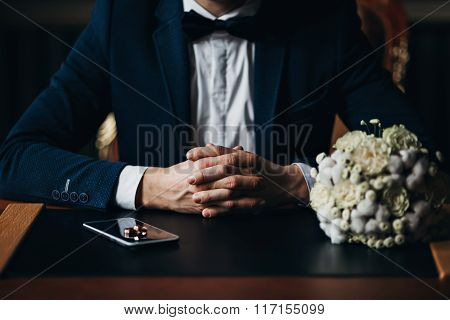 groom with wedding rings and bouquet of flowers