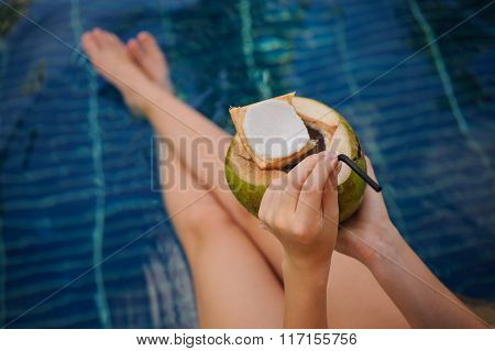 Woman Holding Coconut . Female Legs In Pool Water