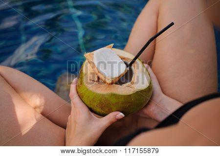 Girl Holding Coconut In Swimming Pool