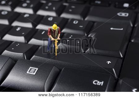 Miniature Worker On Top Of A Black Computer Keyboard
