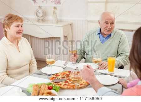 Cute old people are dining with their relatives