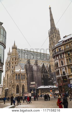 VIENNA AUSTRIA - 5TH JANUARY 2016: A low view of St. Stephen's Cathedral (Stephansdom) and Stephansplatz in Vienna during the winter. Snow can be seen on the building. People can be seen.