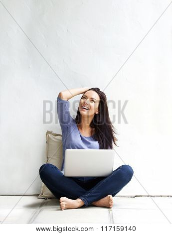 Happy Young Woman Sitting On Floor With A Laptop