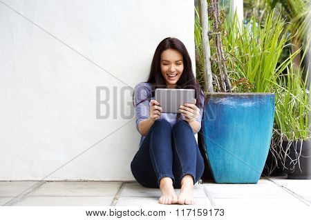 Happy Young Woman Looking At A Digital Tablet And Smiling