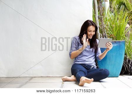 Young Woman Using Tablet And Waving Hello On Chat
