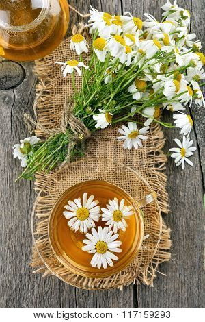 Camomile Tea, Teapot And Flowers On Wooden Background, Top View