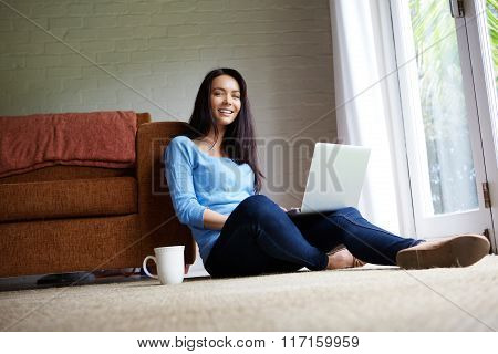 Attractive Young Woman Sitting In Living Room With A Laptop