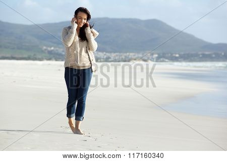 Young Woman Walking And Talking On The Phone At The Beach