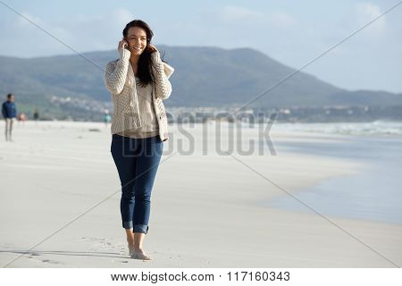 Happy Young Woman Using Mobile Phone At The Beach