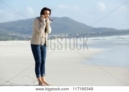 Smiling Young Woman Talking On Cell Phone At The Beach