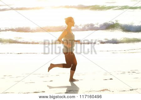 Active Young Woman Running On Beach With Bright Sunlight