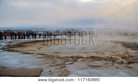 Haukadalur, Iceland-January19, 2016: Tourists waiting for the eruption of Strokkur Geyser in Iceland
