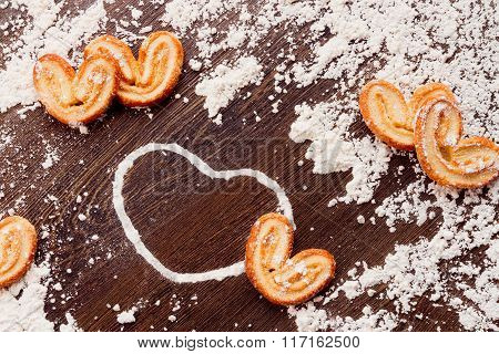 White Heart Shape From Flour With Cookies On Wooden Table. Concept