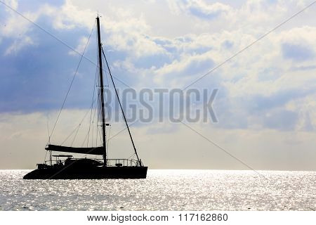 Sail Boat Silhouette In A Sea At Sunset