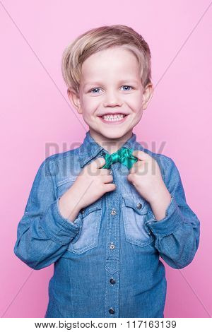 Young beautiful boy with blue shirt and butterfly tie. Studio portrait over pink background