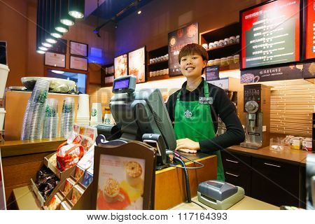 SHENZHEN, CHINA - FEBRUARY 05, 2016: portrait of Starbucks staff. Starbucks Corporation is an American global coffee company and coffeehouse chain based in Seattle, Washington