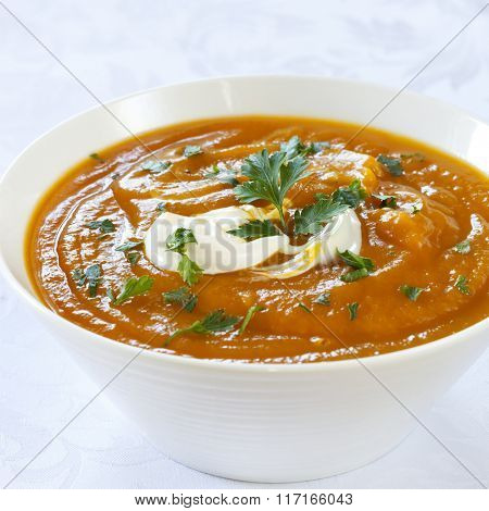 Pumpkin soup in white bowl over brocade background.  Topped with yogurt and parsley.