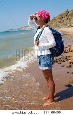 Girl Stands On The Sandy Shore With A Backpack And Looking At The Ocean.