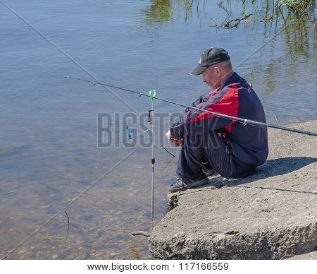 The Fisherman Sits By The River.
