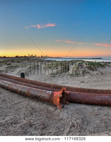 Long dredge pipes lying in the sand.