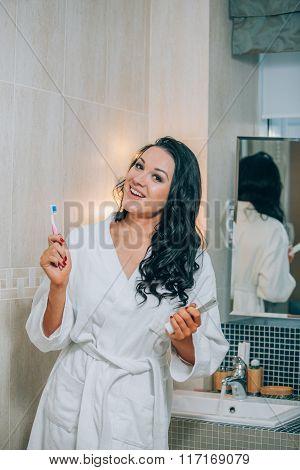 Portrait of attractive woman brushing teeth in bathroom  a white coat. healthy teeth.