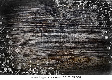 Winter background with snowflakes on wooden texture