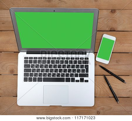 Smart phone near open notebook on wooden background, top view