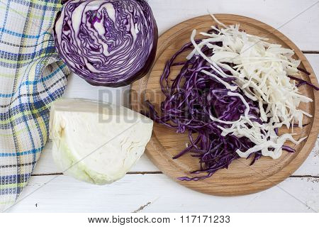 Sliced red cabbage and white cabbage on wooden board
