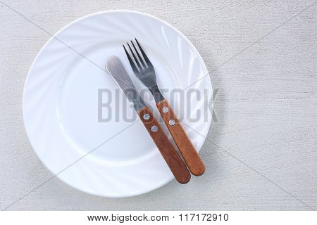 White Dish With A Knife And Fork.
