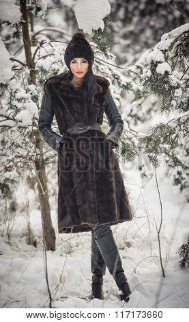 Beautiful woman in long black fur coat and cap enjoying the winter scenery in forest. Brunette girl