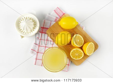 bowl of freshly squeezed lemon juice, lemon squeezer and ripe lemons on wooden cutting board