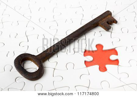 Single key resting on jigsaw puzzle