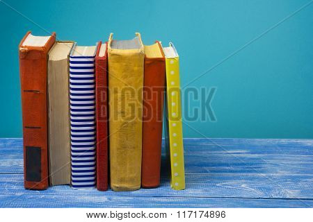 Stack of hardback books on wooden table. Back to school. Copy space for text