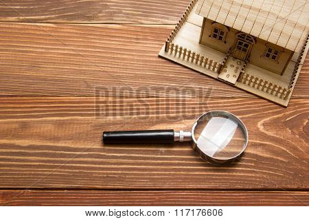 Real Estate Concept. Model house and magnifying glass on wooden table. Top view.