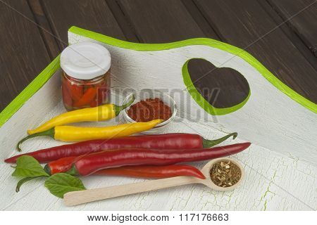 Chili peppers on white wooden platter.