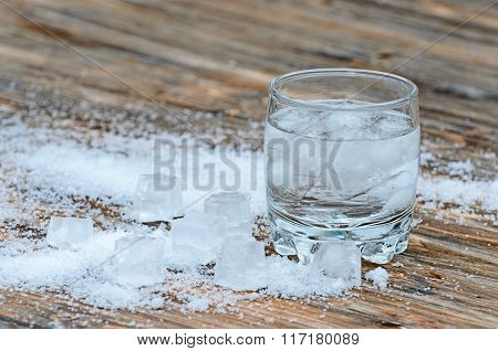 a glass of water with iceon the wooden  background