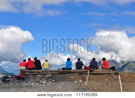 Undefined People Sitting On The Bench In Mountains