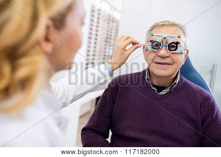 Male senior in eye clinic examine eyes