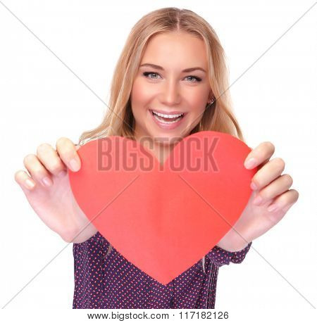 Portrait of attractive cheerful woman holding in hands red heart shaped greeting card for Valentine day, isolated on white background