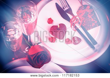 Beautiful festive table setting for Valentine day, luxury white utensil, two wine glasses decorated  with red rose and heart shaped candle, romantic dinner