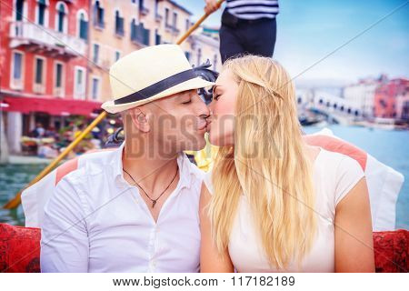 Portrait of happy loving couple in romantic honeymoon, kissing on a gondola, vacation in Italy, enjoying holidays in Italy, Europe
