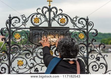 Woman Touching The Sculpture Of Saint Jan Nepomuk On The Charles Bridge In Prague