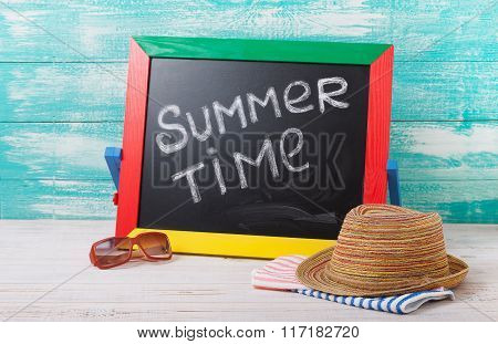 Blackboard with text it's summer time, accessories sunglasses, hat, towel on wooden deck