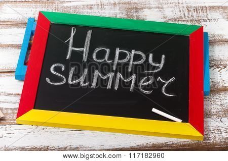 Blackboard with text it's Happy summer on wooden deck