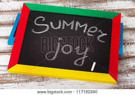 Blackboard with text it's summer Joy on wooden deck