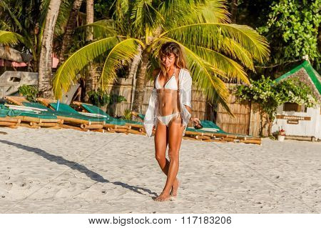 outdoor portrait of young happy girl in bikini on tropical sea background, holiday image