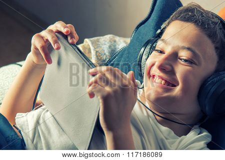 Young boy lying listening to music or have an e-learning class on his tablet computer attached to a