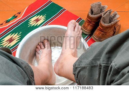 Man Warms His Feet In A Basin Of Water
